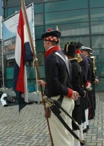 """Equipage De Delft en de hoornblazers van het Korps Mariniers, """"in rust"""" met de handen op de rug."""